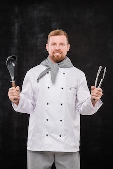Młody wesoły kucharz w mundurze trzymając naczynia kuchenne, stojąc w izolacji na czarnym tle