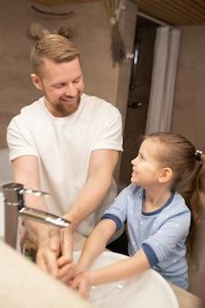 Młody wesoły mężczyzna i jego urocza córeczka w piżamie, patrząc na siebie, stojąc w łazience i myjąc ręce