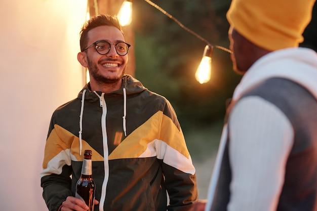 Młody wesoły mężczyzna rasy mieszanej z butelką piwa rozmawia ze swoim afrykańskim przyjacielem, jednocześnie ciesząc się imprezą na świeżym powietrzu przy światłach i muzyce