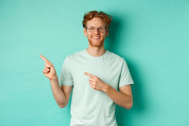 Młody wesoły mężczyzna z krótkimi rudymi włosami i okularami, wskazujący palcem w lewo w miejsce, uśmiechnięte białe zęby, pokazujący reklamę, miętowe tło.