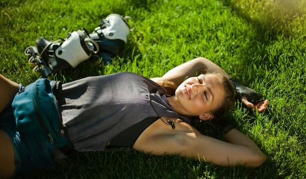 Młody wesoły sport rolkarz kobieta odpoczywa leżąc na trawie trawnik w parku i słucha muzyki w słuchawkach
