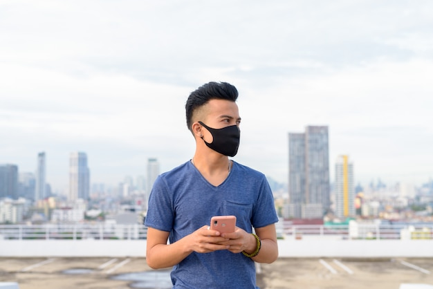 Młody wielo- etniczny mężczyzna z maskowym główkowaniem podczas gdy używać telefon przeciw widokowi miasto