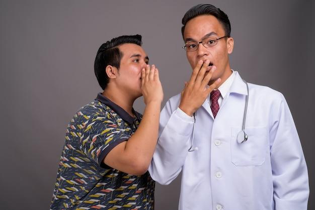 Młody wieloetniczny mężczyzna i młody indianin lekarz przeciw szarej ścianie