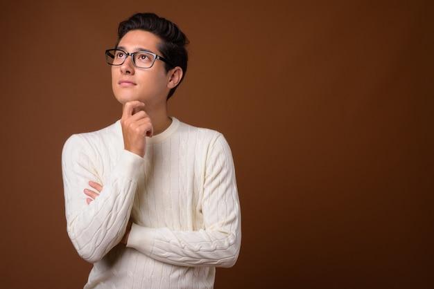 Młody wieloetniczny przystojny mężczyzna na brązowym tle