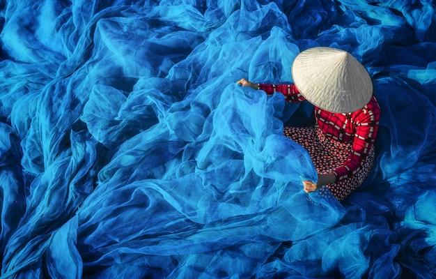 Młody wietnamski kobiety obsiadanie naprawia ryba sieć w ranku, tradycyjny rybak.