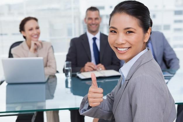 Młody wnioskodawca daje kciuk w górę po uzyskaniu pracy