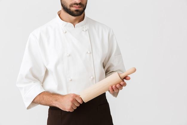 Młody wódz w mundurze kucharza trzymający drewniany wałek do ciasta na białym tle nad białą ścianą