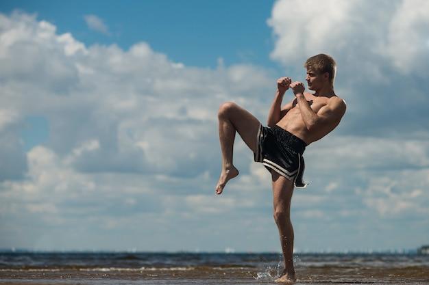 Młody wojownik kopie, ćwiczenia na świeżym powietrzu, kopnięcie kolanem