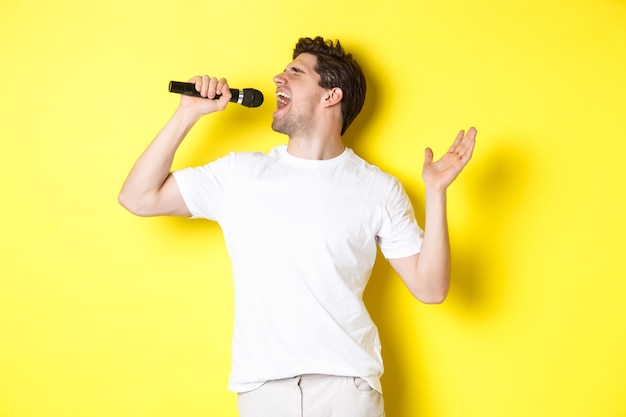 Młody wokalista trzymający mikrofon, osiągający wysoki dźwięk i śpiewający karaoke, stojący na żółtym tle.