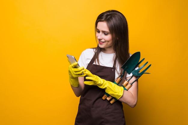 Młody womang ardener wpisując w telefonie trzymając narzędzia na białym tle
