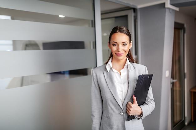Młody wspaniały uśmiechnięty sukces kaukaski bizneswoman pozuje w hali firmy i trzymając w rękach schowek.
