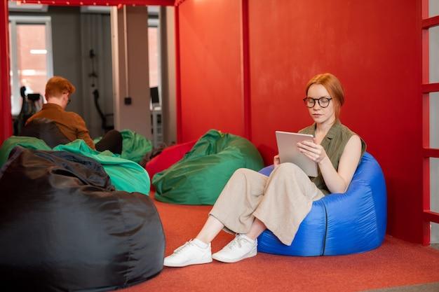 Młody współczesny bizneswoman w casualwear przy użyciu mobilnego gadżetu siedząc w wygodnym fotelu worek fasoli na czerwonej ścianie w biurze