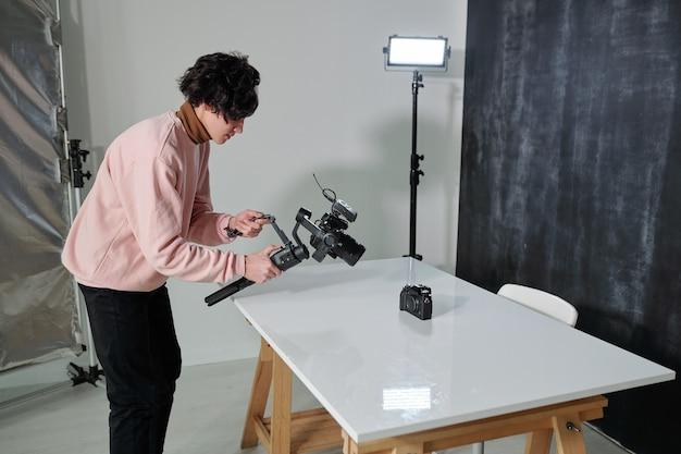 Młody współczesny bloger wideo z aparatem fotografujący nowy sprzęt fotograficzny na biurku w studio