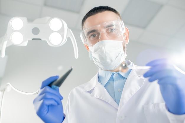 Młody współczesny dentysta w masce, rękawiczkach i białym fartuchu trzyma wiertło i lusterko, pochylając się nad pacjentem przed zabiegiem