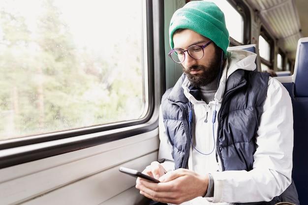 Młody współczesny mężczyzna w okularach i brodzie siedzi w wagonie pociągu ze słuchawkami i patrzy na smartfona. miejsce na tekst.