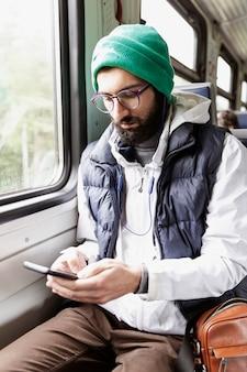 Młody współczesny mężczyzna w okularach i brodzie siedzi w wagonie pociągu ze słuchawkami i patrzy na smartfona. pionowy.