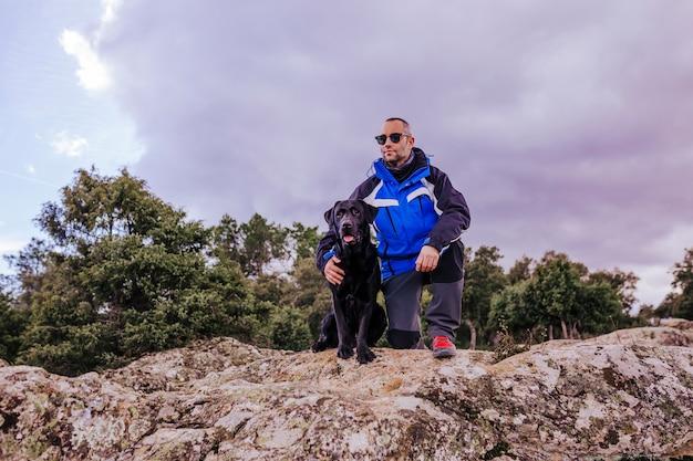 Młody wycieczkowicz mężczyzna przy górą z cześć czarnym labradorem na górze skały. pochmurny zimowy dzień