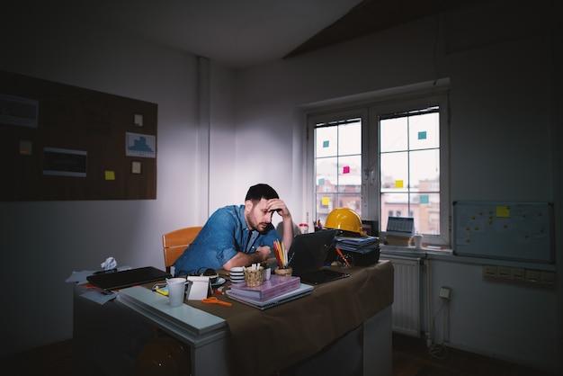 Młody wyczerpany, rozczarowany biznesmen szuka rozwiązania problemu, opierając głowę na dłoni, pozostając po normalnym czasie pracy w ciemnym biurze.