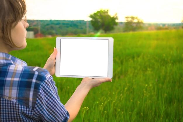 Młody wykonawca opracowuje koncepcję planu budowy, młoda dziewczyna trzyma ekran tabletu z makietą, tło firld natue, skopiuj zdjęcie miejsca