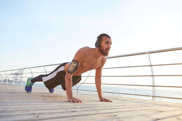 Młody wysportowany brodacz słucha ulubionych piosenek na słuchawkach, poranne ćwiczenia nad morzem, robi pompki, trzyma deskę, rozgrzewa się po bieganiu.