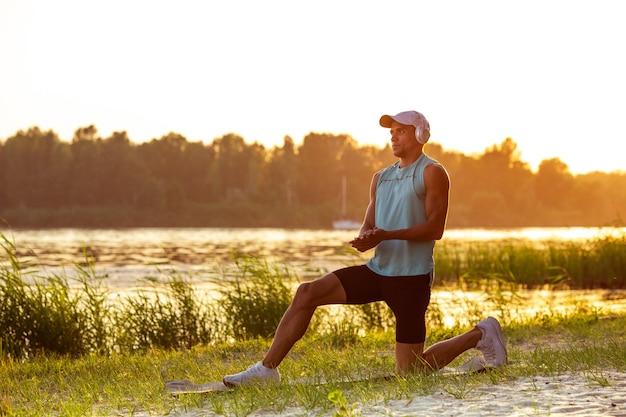 Młody wysportowany mężczyzna ćwiczący słuchanie muzyki nad rzeką na świeżym powietrzu