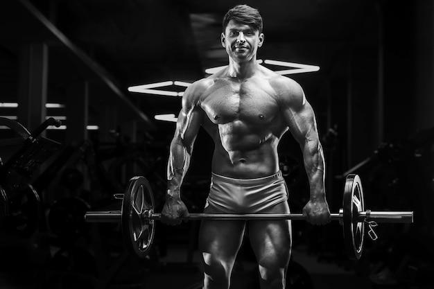 Młody wysportowany mężczyzna pompujący mięśnie na siłowni podczas treningu koncepcja sportu i opieki zdrowotnej
