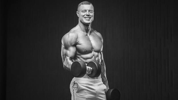 Młody wysportowany mężczyzna pompujący mięśnie na siłowni podczas treningu sport i opieka zdrowotna koncepcja backgroun