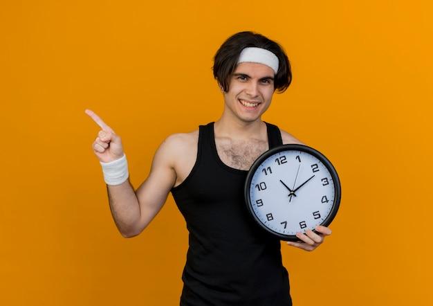 Młody wysportowany mężczyzna ubrany w odzież sportową i opaskę na głowę, trzymający zegar ścienny wskazujący palcem wskazującym w bok, uśmiechnięty stojący