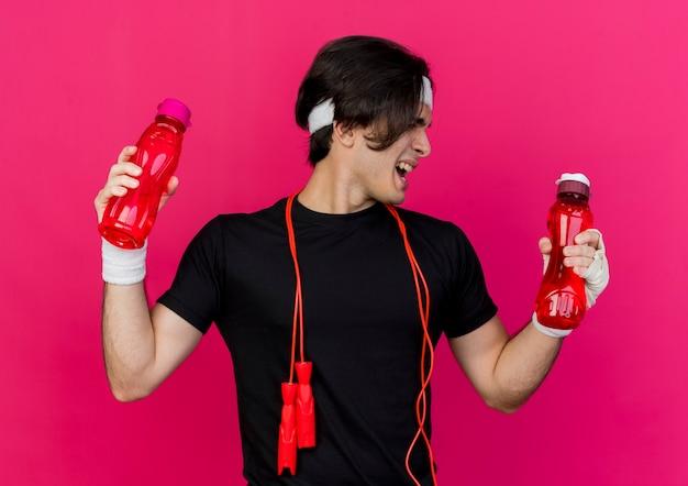 Młody wysportowany mężczyzna ubrany w odzież sportową i opaskę na głowę ze skakanką na szyi, trzymając dwie butelki wody, patrząc na jedną z butelek z zirytowanym wyrazem twarzy