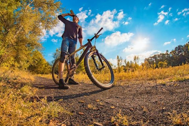 Młody wysportowany mężczyzna w czarnym t-shircie, niebieskich dżinsowych spodenkach i nakolannikach na sportowym rowerze pije wodę z shakera w kolorową jesień z jasnym niebem.