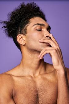 Młody wysportowany mężczyzna z palcami na twarzy portret transseksualny styl mody strzał model płci trans trans