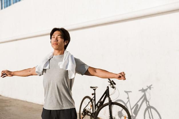 Młody wysportowany rowerzysta ćwiczący na świeżym powietrzu, rozciągający ręce