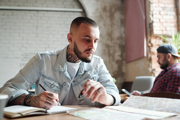 Młody wytatuowany facet w dżinsowej kurtce siedzi przy stole w kawiarni i robi notatki podczas analizy trasy przy użyciu papierowej mapy