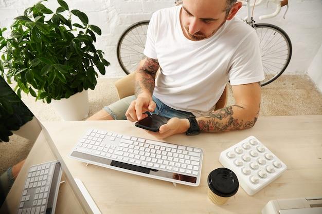 Młody wytatuowany freelancer w pustej białej koszulce używa swojego telefonu komórkowego w pobliżu komputera w domu przed murem i zaparkowanym zabytkowym rowerem, czas letni
