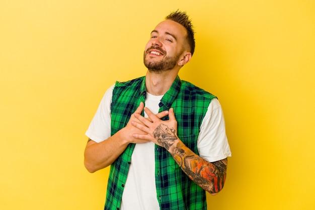 Młody wytatuowany kaukaski mężczyzna na żółtej ścianie ma przyjazny wyraz, przyciskając dłoń do piersi. koncepcja miłości.