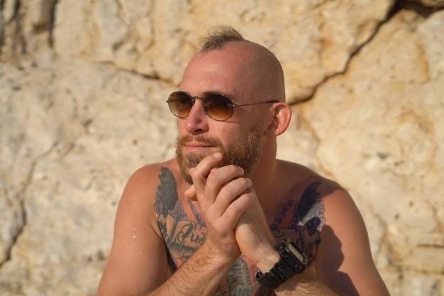 Młody wytatuowany sportowy mężczyzna na plaży w gorący letni słoneczny dzień w górach pozowanie w okularach przeciwsłonecznych