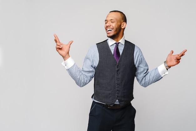 Młody zabawny biznesmen afroamerykański trzymający kciuki, pragnący, mając nadzieję na najlepsze, cud na szarej ścianie