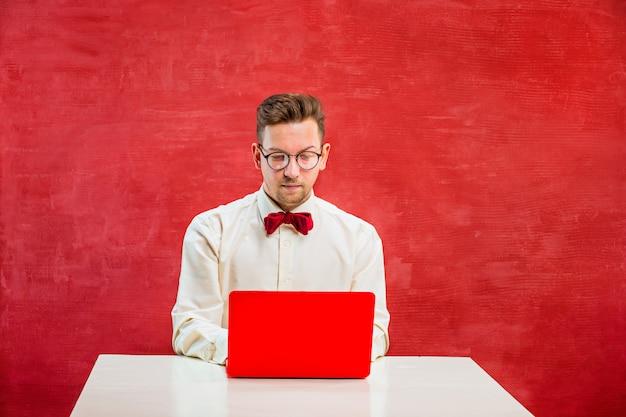 Młody zabawny człowiek z laptopem w dzień świętego walentego