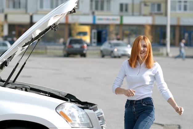 Młody zabawny uśmiechnięty kierowca kobieta w pobliżu zepsutego samochodu z pękniętym kapturem