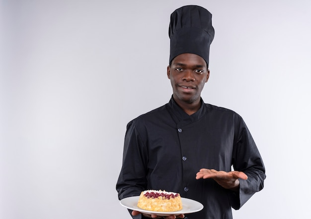 Młody zadowolony afro-amerykański kucharz w mundurze szefa kuchni trzyma ciasto na talerzu i wskazuje ręką na białym z miejsca na kopię