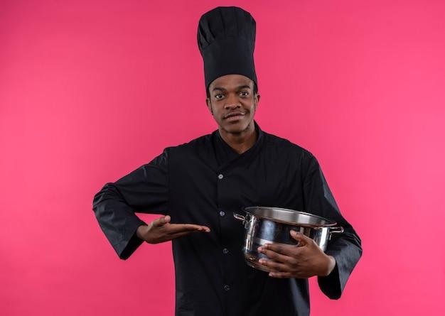 Młody zadowolony afro-amerykański kucharz w mundurze szefa kuchni trzyma rondel i trzyma rękę prosto na białym tle na różowej ścianie