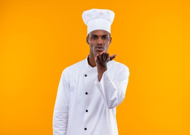 Młody zadowolony afro-amerykański kucharz w mundurze szefa kuchni wysyła pocałunek na białym tle na pomarańczowej ścianie