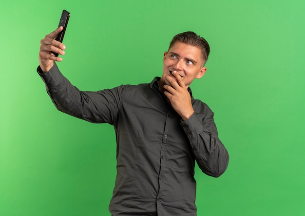 Młody zadowolony blondynka przystojny mężczyzna patrzy na telefon przy selfie i kładzie rękę na ustach odizolowanych na zielonej przestrzeni z miejsca na kopię