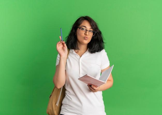 Młody zadowolony całkiem kaukaska uczennica wskazuje piórem w okularach iz powrotem trzymając notebook na zielono z miejsca na kopię