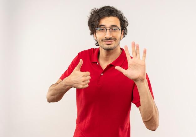 Młody zadowolony człowiek w czerwonej koszuli z okularami optycznymi kciuki do góry i podnosi rękę na białym tle na białej ścianie