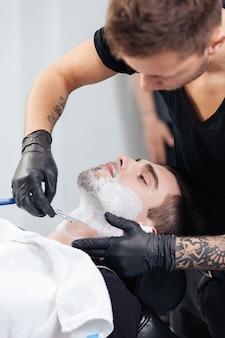 Młody zadowolony klient podczas golenia brody w salonie fryzjerskim