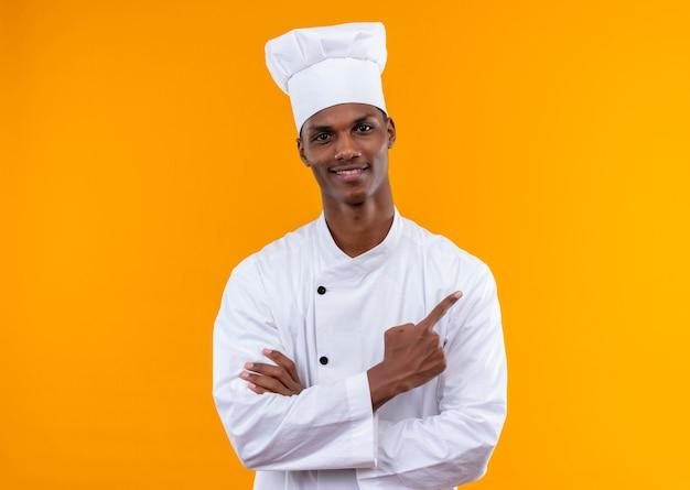 Młody zadowolony kucharz afroamerykański w mundurze szefa kuchni krzyżuje ramiona i wskazuje bok odizolowany na pomarańczowej ścianie
