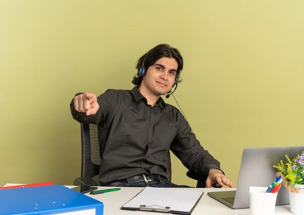 Młody zadowolony pracownik biurowy mężczyzna na słuchawkach siedzi przy biurku z narzędzi biurowych za pomocą laptopa, wskazując na aparat samodzielnie na zielonym tle z miejsca na kopię