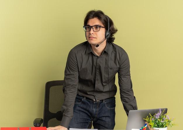 Młody zadowolony pracownik biurowy mężczyzna na słuchawkach stoi przy biurku za pomocą laptopa i patrzy na bok