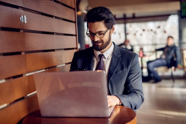 Młody zadowolony stylowy uśmiechnięty przystojny brodaty biznesmen w garniturze patrząc na laptopa obok drewnianej ściany w kawiarni lub restauracji.